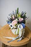 Цветки в вазе на белых предпосылке и деревянном столе Стоковое Изображение