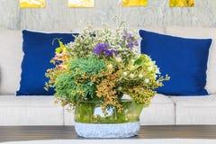 Цветки в вазе на таблице перед софой Стоковые Изображения RF