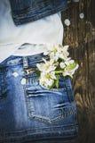 цветки в кармане юбки джинсовой ткани на деревянной предпосылке стоковое фото