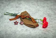 Цветки гвоздики, лента Джордж, крышка фуража, заказы и медали Стоковая Фотография