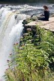 Цветки горы и девушка мечтая над водопадом Стоковое Изображение RF