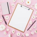 Цветки доски сзажимом для бумаги, тетради, ручки и белых роз на розовой предпосылке Плоское положение, взгляд сверху Женская пред Стоковая Фотография RF