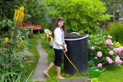 Цветки девушки моча в саде Стоковая Фотография RF