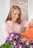 Цветки девушки моча на балконе Стоковые Фотографии RF