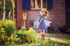 Цветки девушки ребенка моча в саде лета, маленьком хелпере Стоковые Изображения