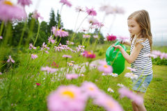 Цветки и заводы прелестной маленькой девочки моча Стоковые Изображения RF