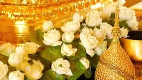 Цветки и золотые украшения на алтаре Красивые цветки белого лотоса и золотые королевские орнаменты помещенные на традиционном сток-видео