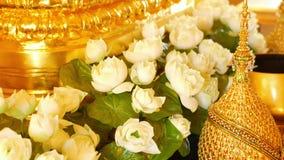 Цветки и золотые украшения на алтаре Красивые цветки белого лотоса и золотые королевские орнаменты помещенные на традиционном акции видеоматериалы