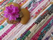 Цветки и камешки на красочной циновке стоковое фото