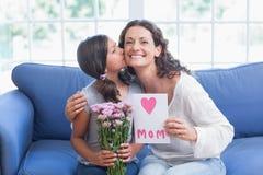 Цветки и карточка милой девушки предлагая к ее матери Стоковая Фотография RF