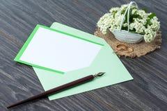 Цветки и конверт на деревянной предпосылке Стоковая Фотография RF