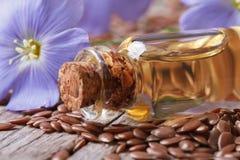 Цветки и семя льна, масло в макросе стеклянной бутылки стоковые фото