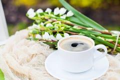Цветки колокола весны букета белые и кофейная чашка на таблице в gar Стоковое Изображение RF