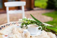 Цветки колокола весны букета белые и кофейная чашка на таблице в gar Стоковая Фотография