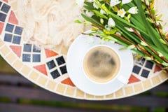 Цветки колокола весны букета белые и кофейная чашка на таблице в gar Стоковое Фото