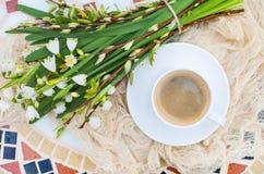 Цветки колокола весны букета белые и кофейная чашка на таблице в gar Стоковое Изображение