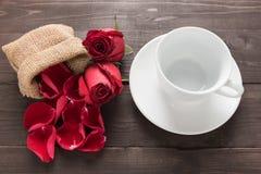 Цветки красных роз и чашка на деревянной предпосылке Стоковая Фотография RF