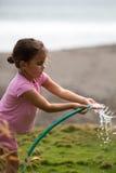 Цветки милой курчавой девушки моча в саде Стоковое Изображение