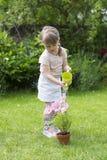 Цветки милой маленькой девочки моча в саде Стоковая Фотография