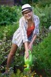 Цветки молодого привлекательного садовника девушки моча Стоковое Изображение