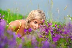 Цветки обнюхивать девушки в лужке Стоковое Изображение