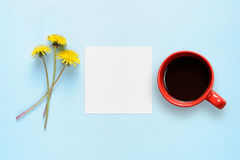 Цветки одуванчика, чистый лист бумаги и кофейная чашка Стоковая Фотография