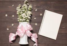 Цветки резца с лентой в вазе рядом с тетради Стоковая Фотография RF