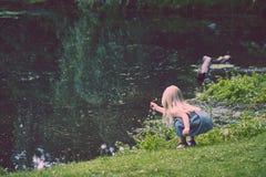 Цветки рудоразборки маленькой девочки на реке в лете Стоковые Фотографии RF