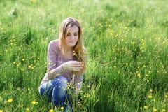 Цветки рудоразборки молодой женщины на луге лета Стоковое Изображение