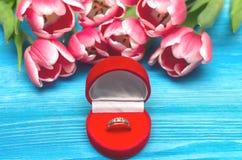 Цветки тюльпана и обручальное кольцо в подарке представляют коробку на деревянной предпосылке Предложение замужества Предложение Стоковые Фотографии RF