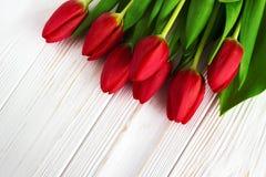 Цветки тюльпана букета красные на старом деревянном столе Справочная информация Eas Стоковая Фотография RF