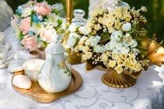 Цветки, чайник, сахар и зефиры на подносе на таблице Стоковые Изображения