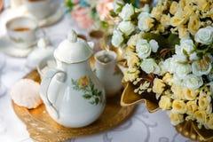 Цветки, чай, зефиры на подносе на таблице Стоковое Фото