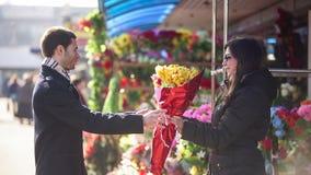 Цветки человека покупая в магазине улицы видеоматериал