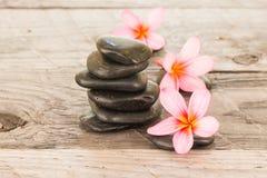 Цветки Plumeria и предпосылка камней черноты деревянная Стоковое Изображение