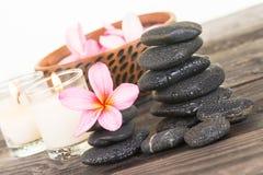 Цветки Plumeria и черные камни на выдержанном конце древесины вверх Стоковые Фотографии RF