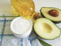 Цветок желтого цвета авокадового масла Cream косметической заботы ингридиента зеленого цвета продукта здоровый на белое деревянно Стоковые Фотографии RF