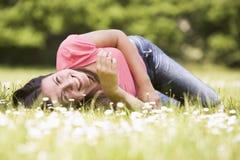цветок лежа outdoors ся женщина стоковое фото rf
