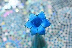 Цветок синего стекла стекловидного ` ` неоновый в вазе с стеклянной предпосылкой таблицы мозаики стоковые изображения rf