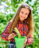 Цветочный горшок владением ребенк ребенка прелестный и инструмент сапки садовничая Садовничать мирное медитативное занятие r стоковое фото rf