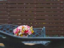 Цветочный горшок на винтажной таблице и стенд в backg сада и половых доск Стоковая Фотография