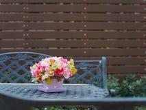 Цветочный горшок на винтажной таблице и стенд в backg сада и половых доск Стоковые Фотографии RF