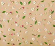 Цветочный узор сделанный из белых цветков весны, листьев зеленого цвета и розовых бутонов на предпосылке коричневой бумаги Плоско Стоковые Изображения