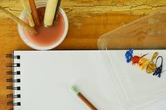 Цвет и белая бумага воды делают эскиз к книге при кисть моя в пластичной чашке Стоковые Изображения