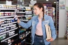 Цвет покупок девушки в стеклянном опарнике в магазине искусства Стоковая Фотография