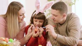 Целая семья украшает одно яйцо на праздник пасхи сток-видео