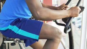 Целевой Афро-американский человек ехать велотренажер в фитнес-клубе, спорте сток-видео