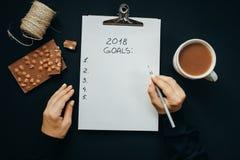 2018 целей перечисляют с руками женщины, карандашем, шоколадом, какао, конусом Стоковая Фотография
