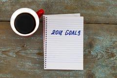 2018 целей перечисляют с тетрадью, чашкой кофе на деревянном столе К Стоковые Изображения RF