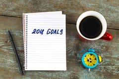 2018 целей перечисляют с тетрадью, чашкой кофе на деревянном столе К Стоковое Изображение